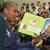 Raja Bell reading to auditorium full of children