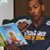 Raja Bell reading with children sitting in front of him