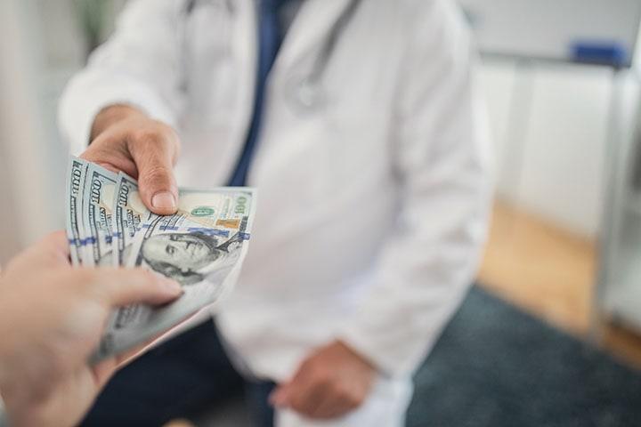 Handing cash to doctor